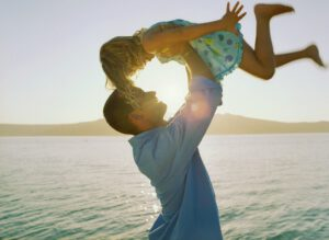 Man Lifting Daughter Into Air